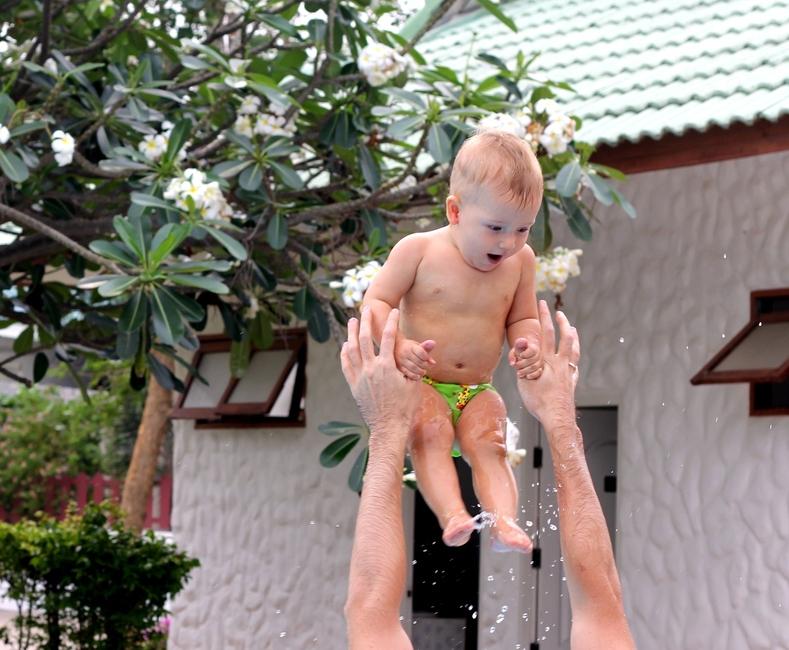 Папа держит ребенка за руки
