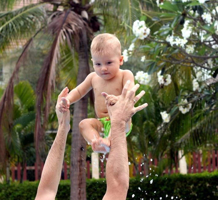 Папа подбрасывает ребенка над собой