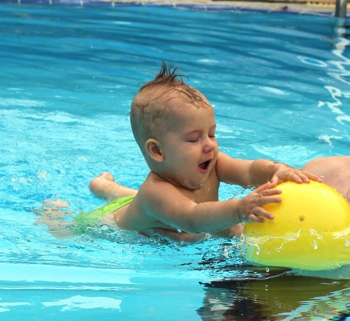 Мальчик 9 месяцев плавает в бассейне с мячом