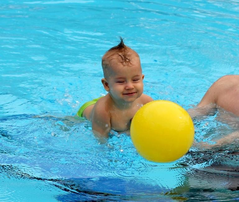 Малыш с мячом в бассейне
