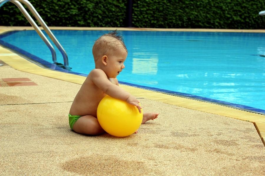 Ребенок с желтым мячом сидит около бассейна