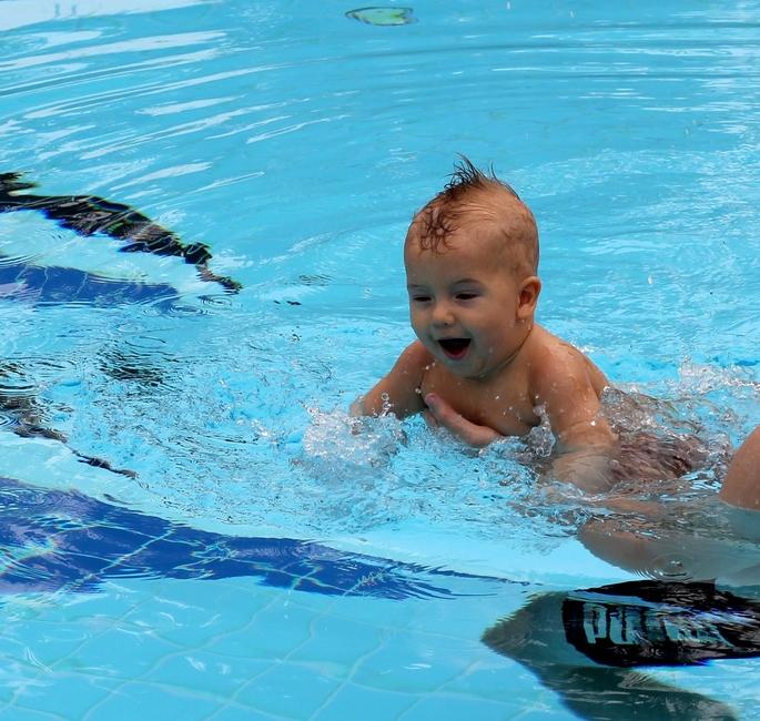 Маленький ребенок плавает в бассейне