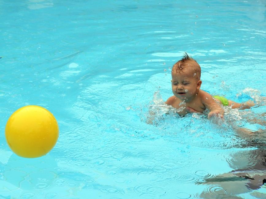 Ребенок плывет за мячом