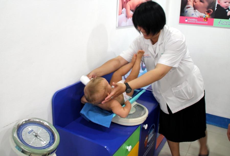 Тайская медсестра взвешивает ребенка