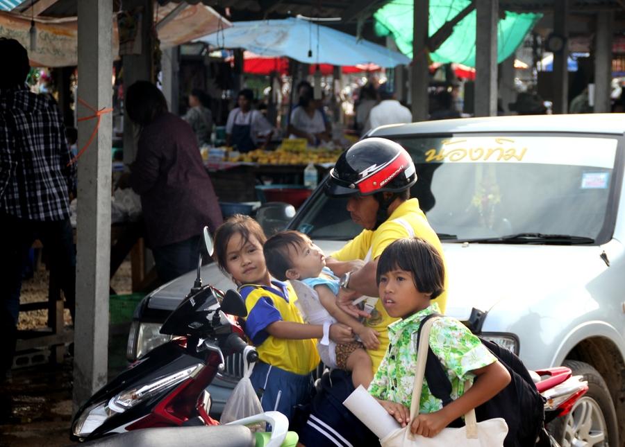 Мужчина с тремя детьми на мотобайке