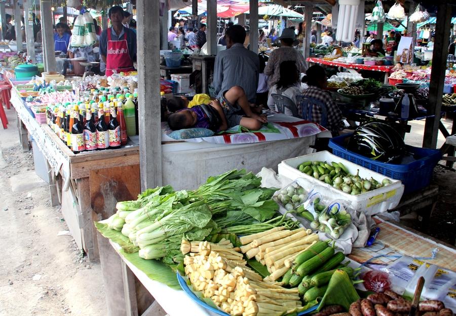 Спящие тайские дети на рынке около овощей