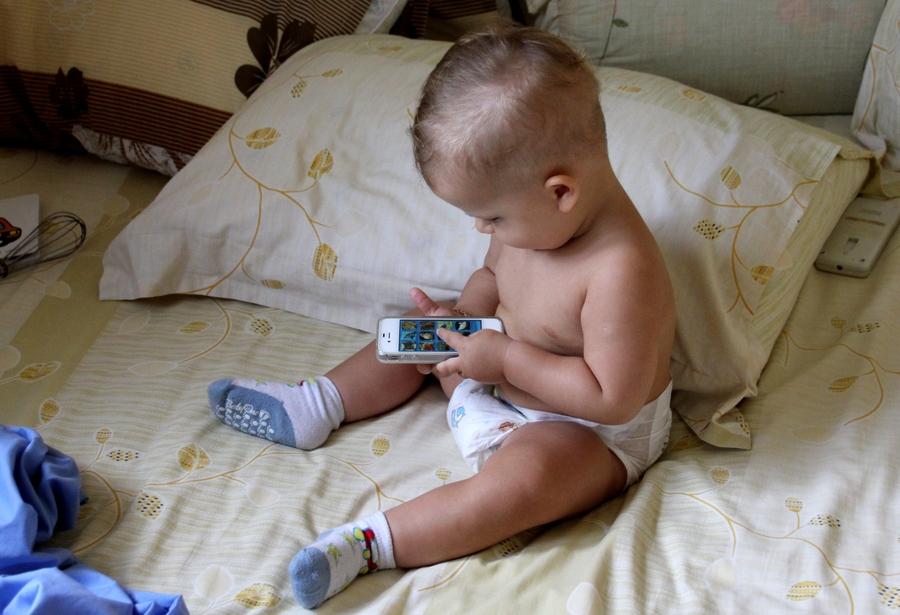Маленький ребенок играет в iPhone