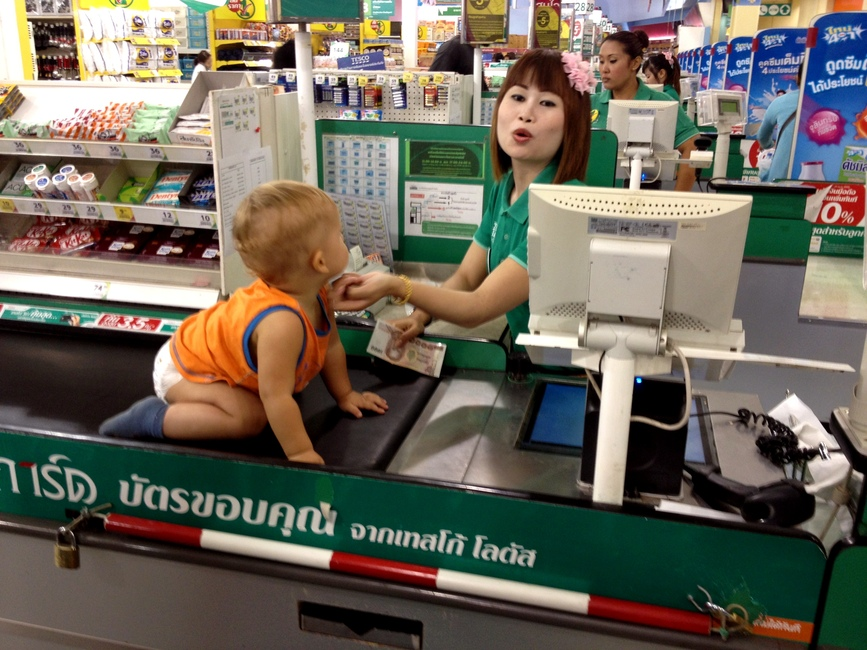 Ребенок на ленте в супермаркете с тайской продавщицей