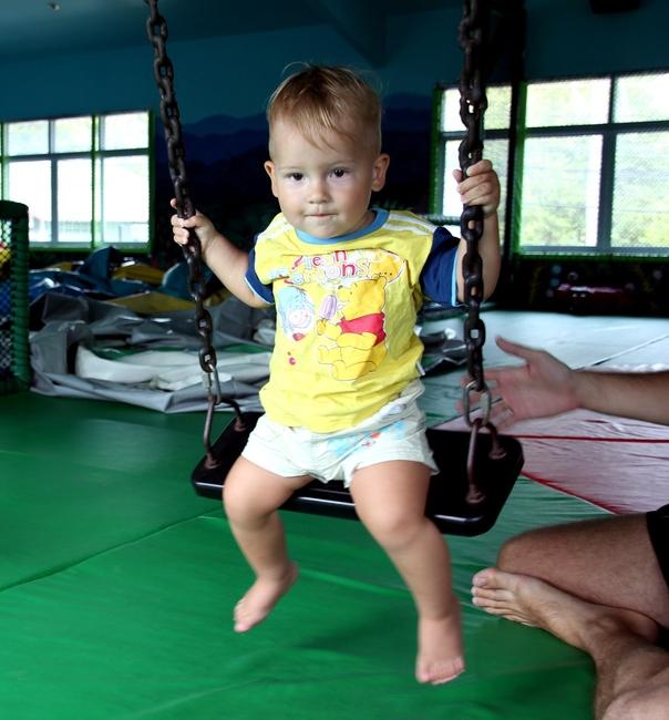 Мальчик 1 год сам катается на качелях
