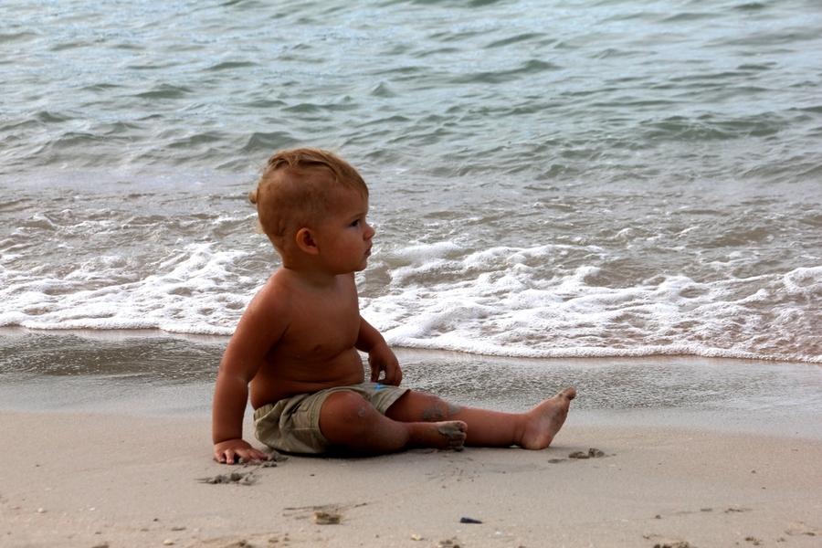 Ребенок 1 год сидит на пляже на острове Самуи