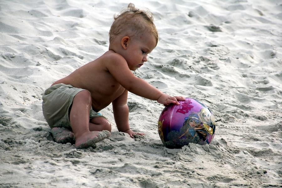Маленький ребенок на пляже играет с мячом
