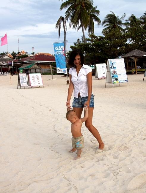 Мама с ребенком гуляют по пляжу в Тайланде
