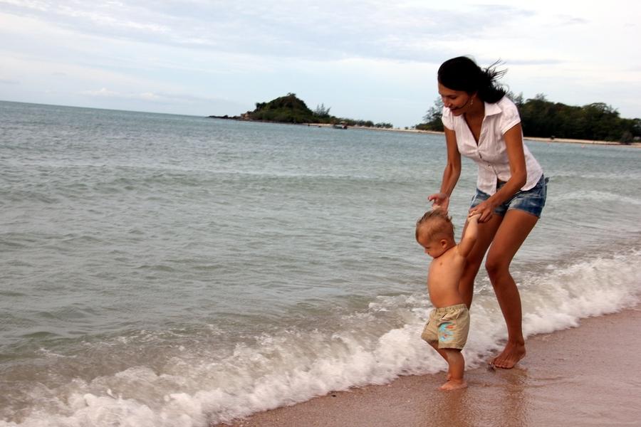 Мама и маленький ребенок на берегу моря на острове Самуи