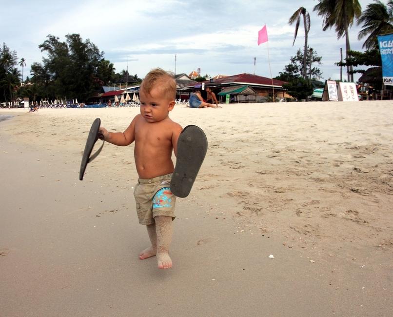 Ребенок 1 год бежит по пляжу со шлепанцами в руках