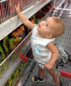 Маленький ребенок в супермаркете в тележке