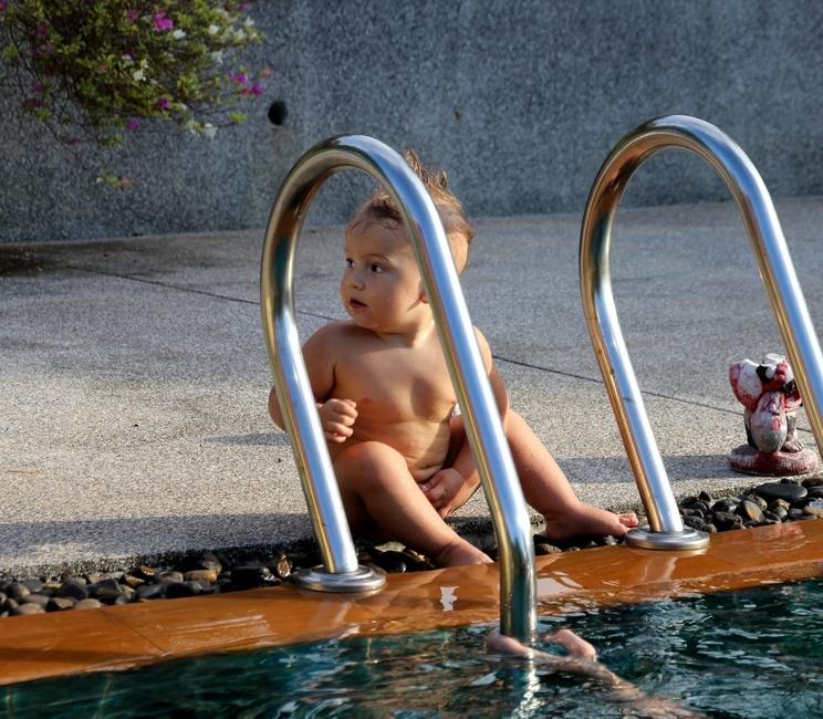 ребенок сидит около бассейна