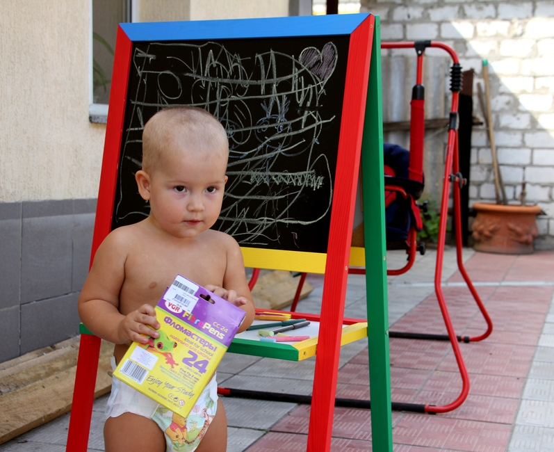 Маленький мальчик с фломастерами около мольберта
