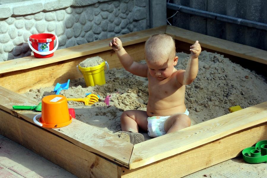 Ребенок 1 год в песочнице играет с песком