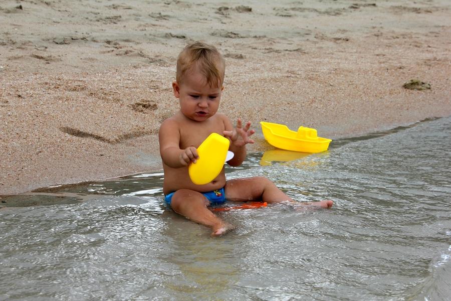 Ребенок на берегу моря играет в кораблики