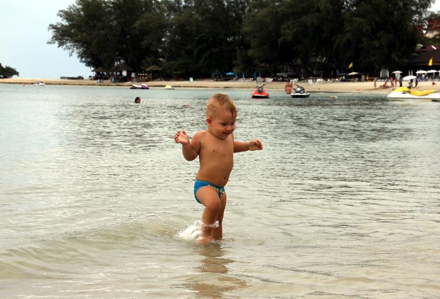 Мальчик 1 год ходит по воде в море в Тайланде