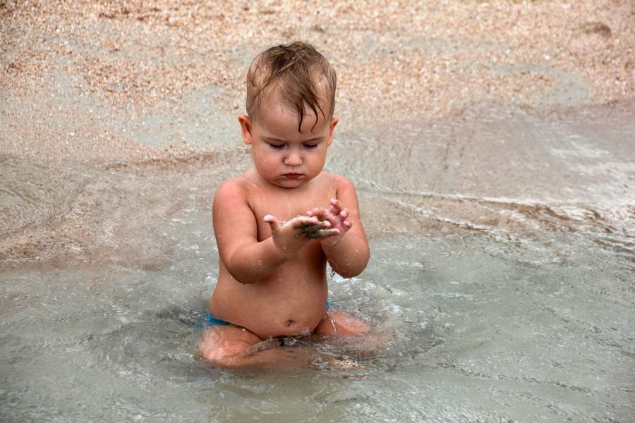 Маленький мальчик сидит в море и изучает песочек