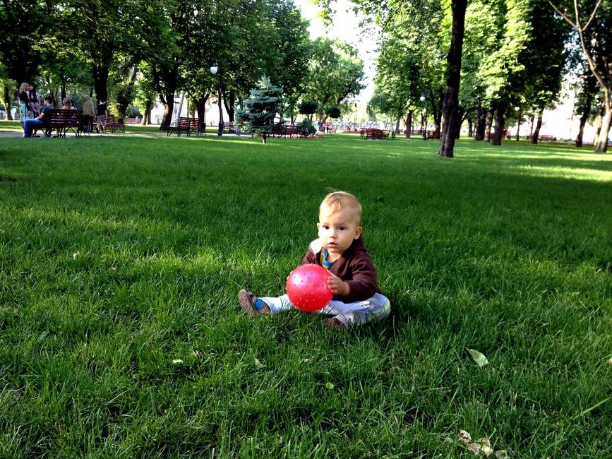 Мальчик 1 год на лужайке с красным мячом