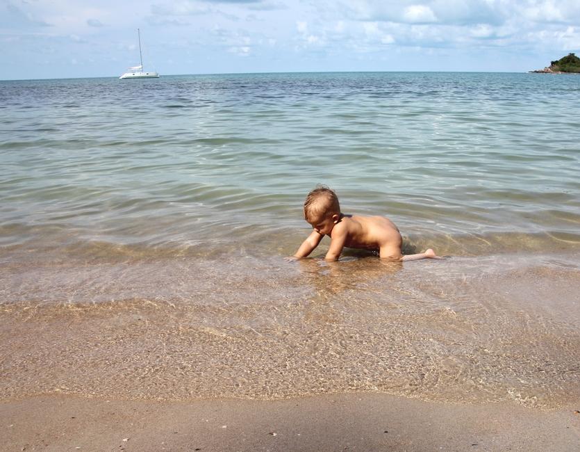 Маленький ребенок купается в море на острове Самуи