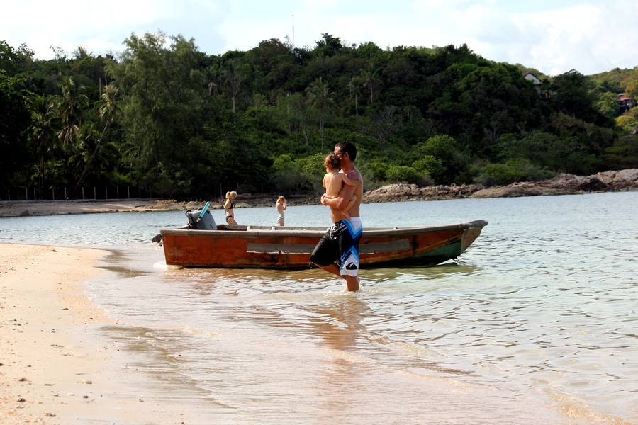 Мужчина выходит из моря с ребенком на руках