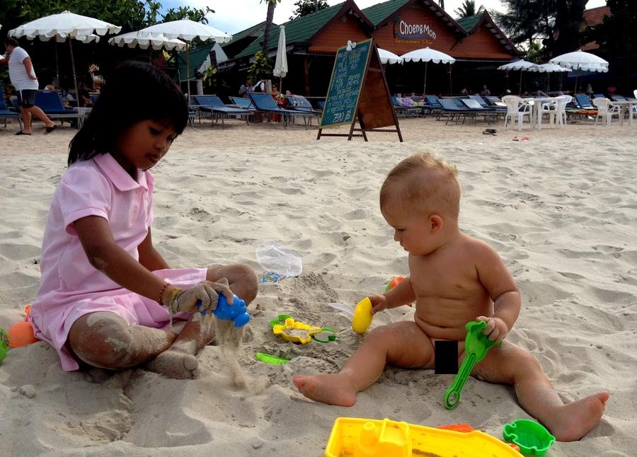 Белый мальчик и девочка азиатка играют на пляже