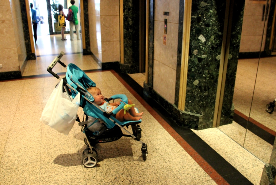 Ребенок в коляске около лифта в Baiyoke Sky Hotel