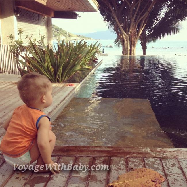 Маленький ребенок на Самуи около бассейна смотрит на море