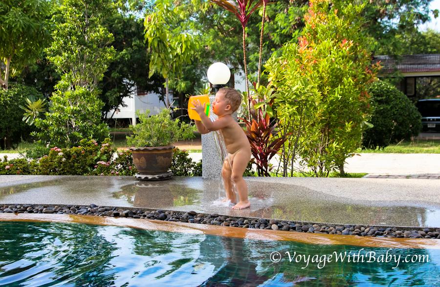 Ребенок обливаетя водой из ведра около бассейна