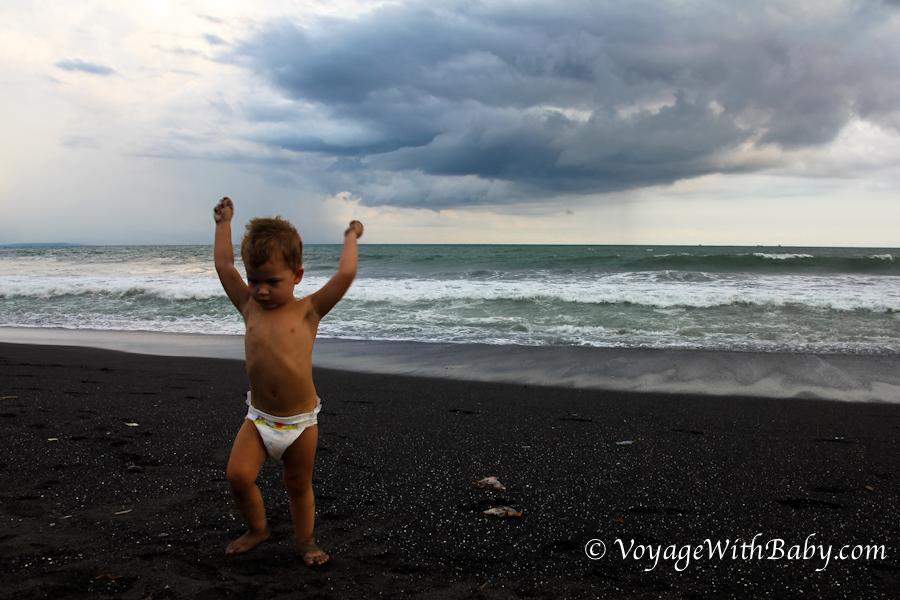 Ребенок на пляже с черным песком Кетевел на Бали