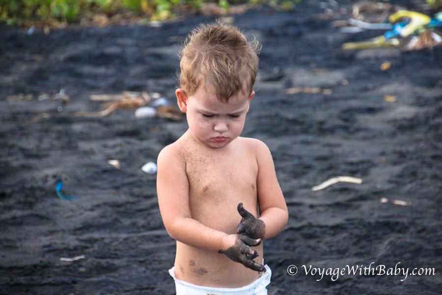 Ребенок играет с черным песком на Бали