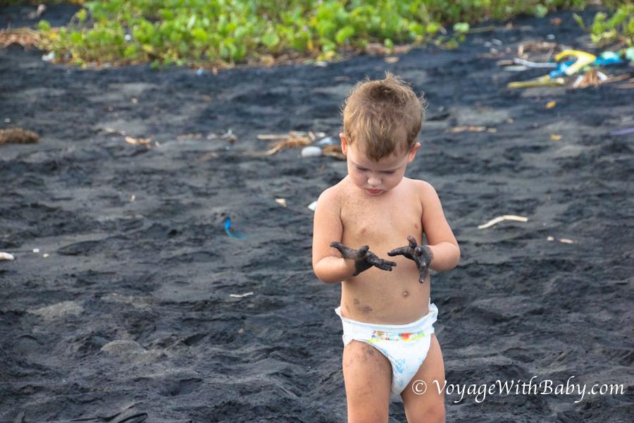 Мальчик на пляже с черным песком на Бали