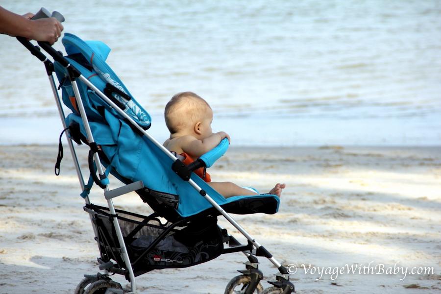 Ребенок в коляске на пляже в Таиланде