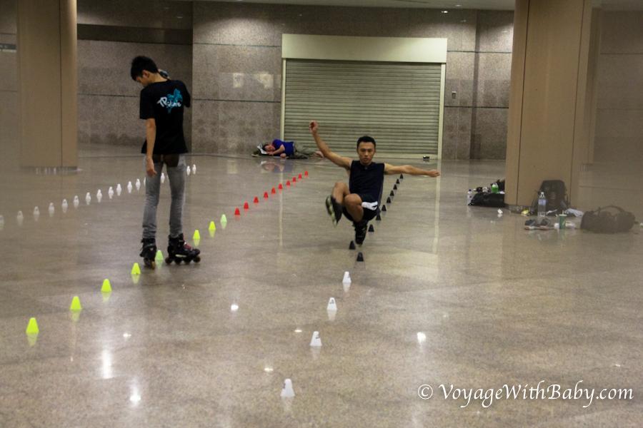 Роллеры и бомж в подземном переходе в Сингапуре