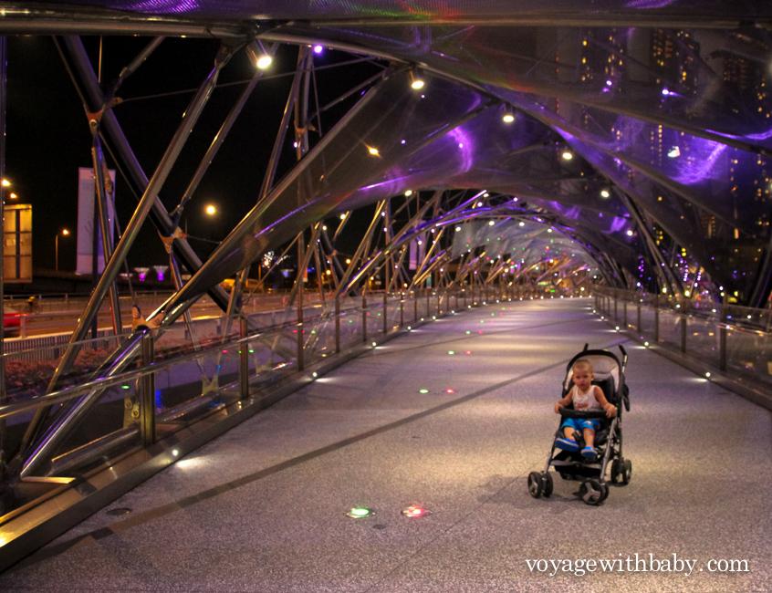 Ребенок в коляске на мосту Хеликс в Сингапуре