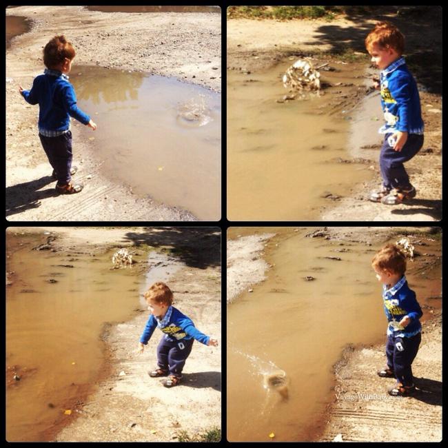 Сынуля бросает камушки в лужу