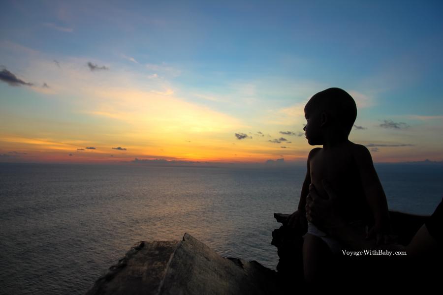 Маленький ребенок любуется закатом на Бали