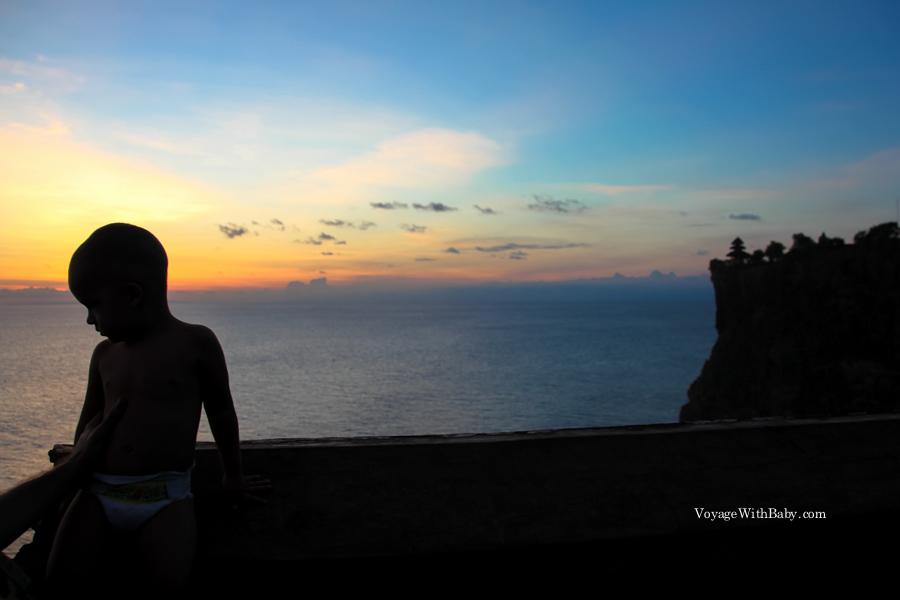Мальчик на закате на краю скалы в Улувату на острове Бали