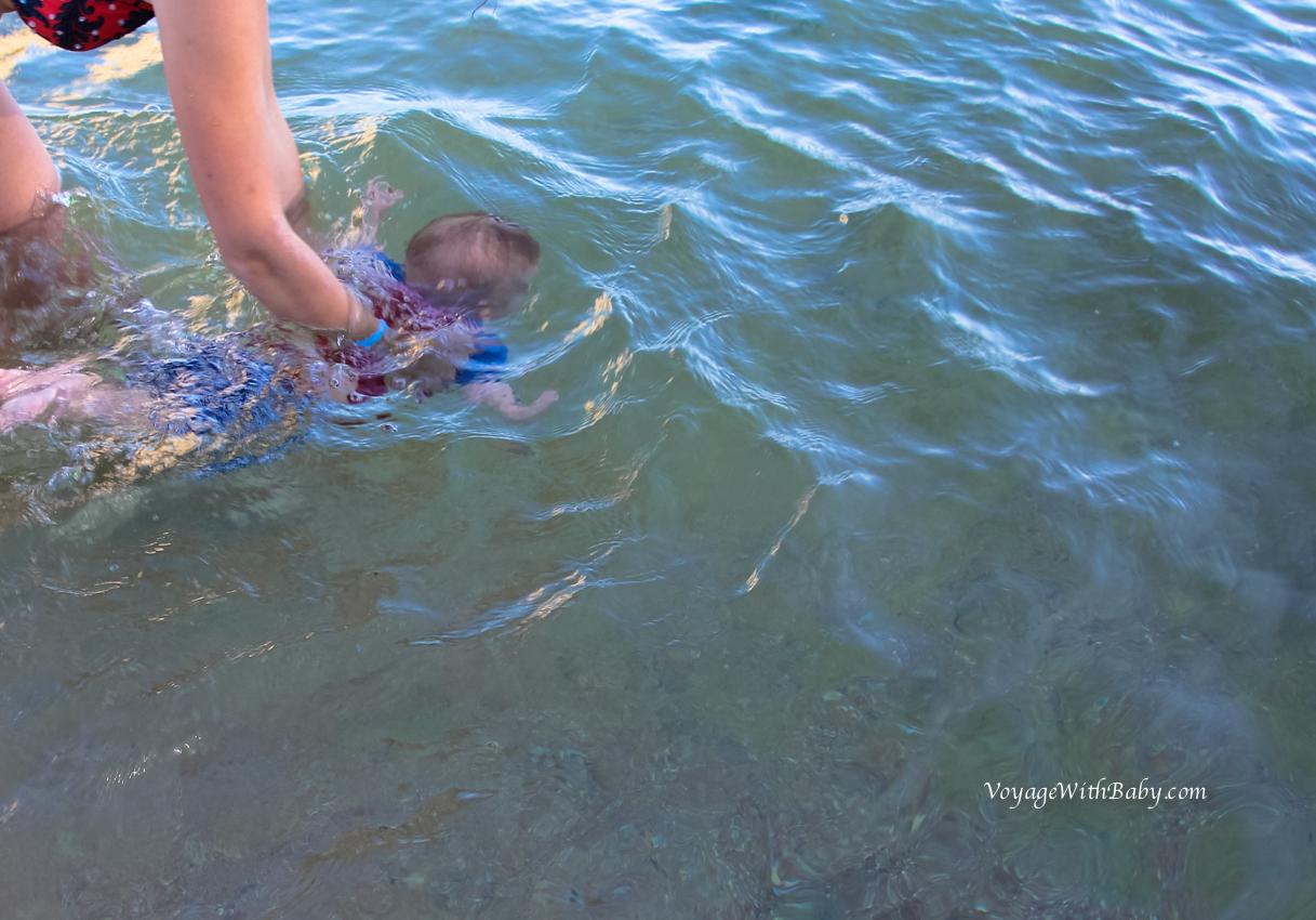 Грудной ребенок ныряет в море