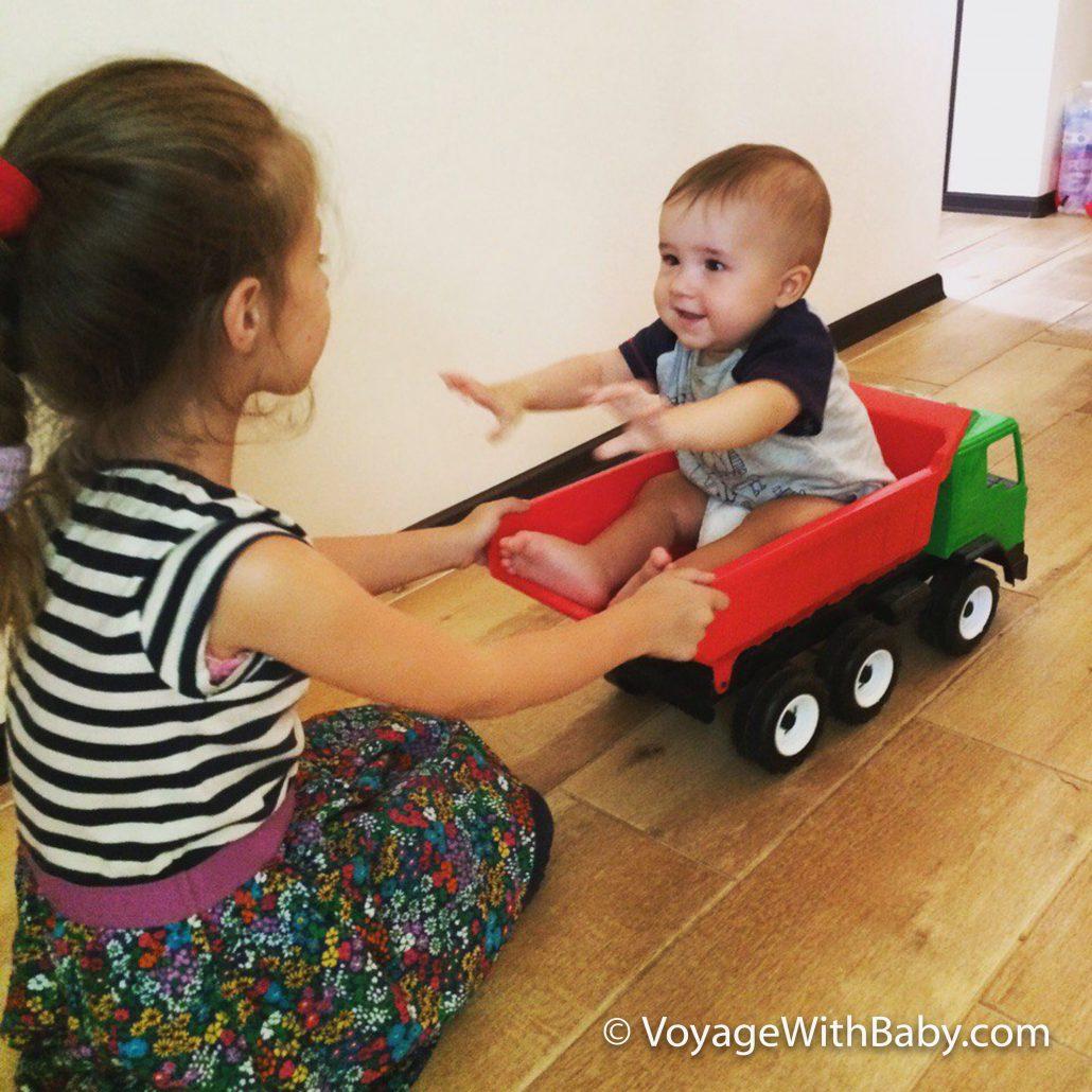 Катание ребенка в игрушечном самосвале